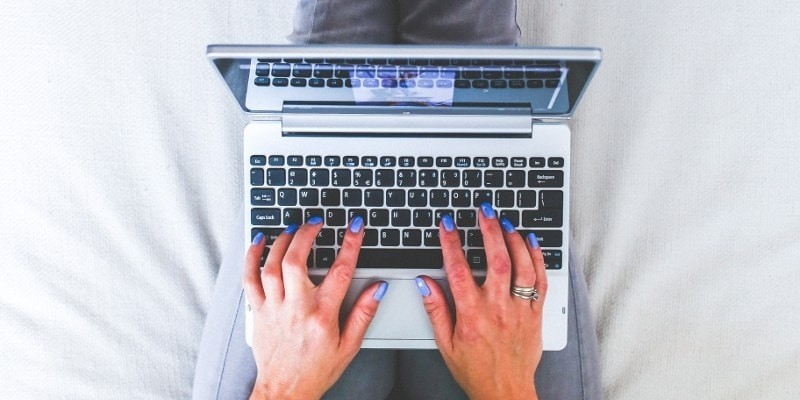 Start a wordpress blog on laptop, woman's hands typing