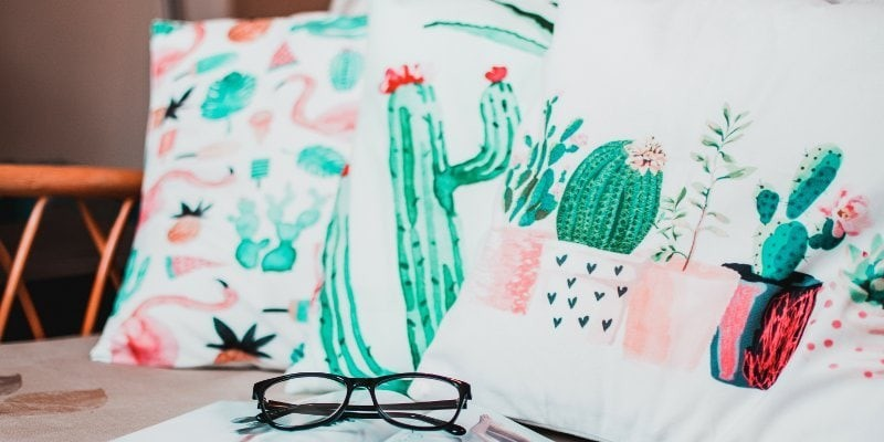 Water color cacti on white pillows on a bench with glasses