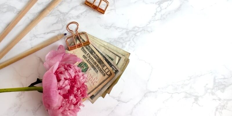 The best tools for bloggers make money blogging header image of pink flower and money paper clipped together
