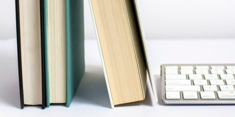 The best tools for bloggers twitter header image of books next to apple mac keyboard