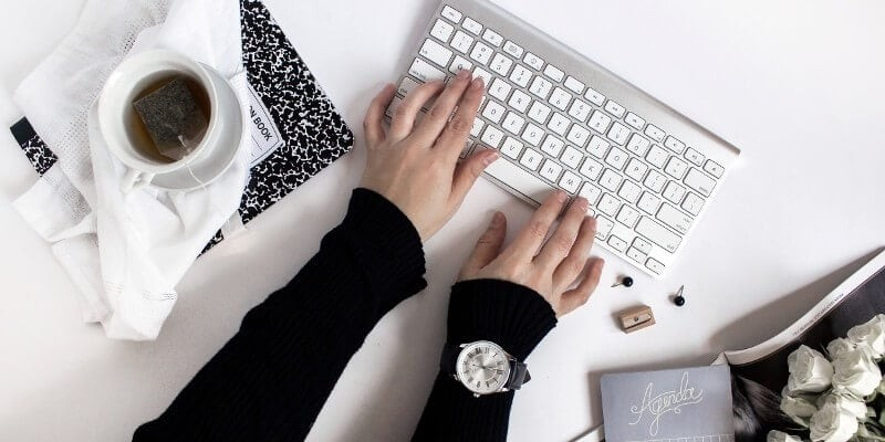 The best tools for bloggers website speed header image of woman typing on silver apple mac keyboard