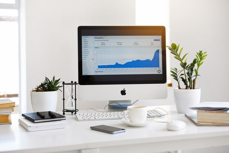 How To Use Pinterest For Business Header Image Of Mac On White Desk With Plants & Notebooks