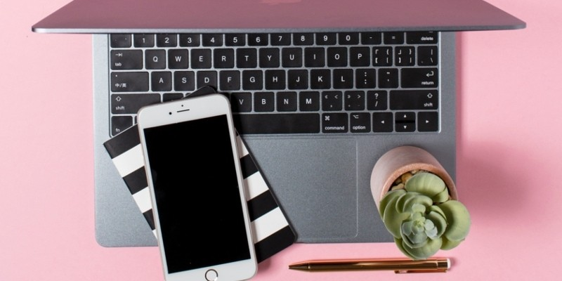Blog Image Mistakes Header Image Of Silver Laptop Open With Striped Notepad, Mobile Phone And Potted Plant