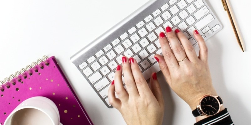 Blog Image Mistakes Of Woman Typing On Keyboard With Peach And Pink Flowers Mug And A Pink Notepad