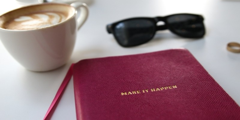Red Notebook With Embossed Make It Happen Text And Coffee Mug