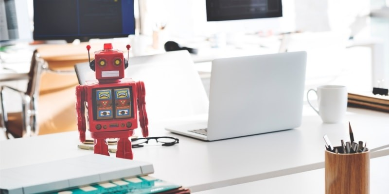 Why Use WordPress For Blogging Header Image Of White Office With Laptop And Red Robot