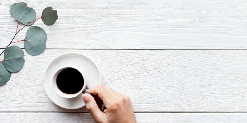 Blogger With A Cup Of Black Coffee In White Mug Against White Washed Wood