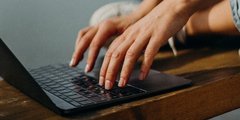 Female Blogger Typing At Her Laptop To Create Her Blog Content