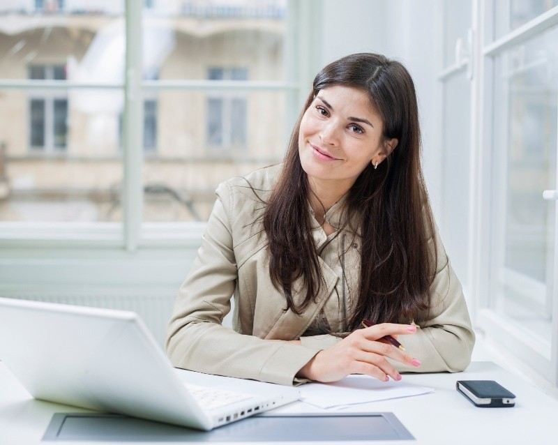 Female Blogger Using Laptop In Bright Office